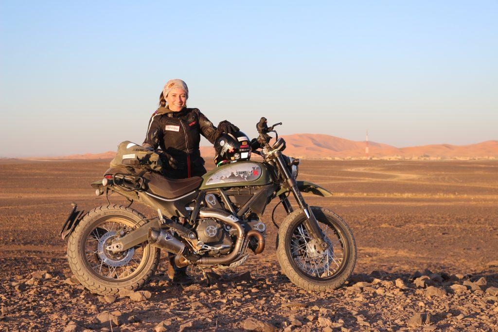 Scrambler posando con dunas al fondo sobre tierra 2
